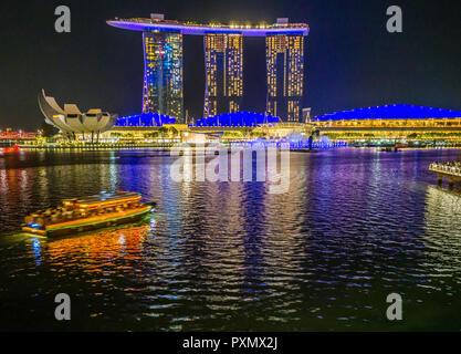 Ansicht bei Nacht in Singapur Marina Bay in Richtung der beleuchteten Marina Bay Sands Hotel. - Stockfoto