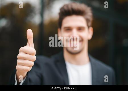 Sieger. Erfolg. Brünette junge Mann im Geschäft Kleidung im Büro Bezirk lächelt in die Kamera und gibt Daumen nach oben. Happy Guy anzeigen Geste der Zustimmung - Stockfoto