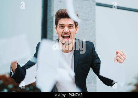 Wütend, wütend, männliche Mitarbeiter werfen zerknittertes Papier, Nervenzusammenbruch bei der Arbeit, schreiend in Wut, Stress Management, psychischen Störungen Probleme, verloren, Temperament, Reaktion auf Fehler - Stockfoto