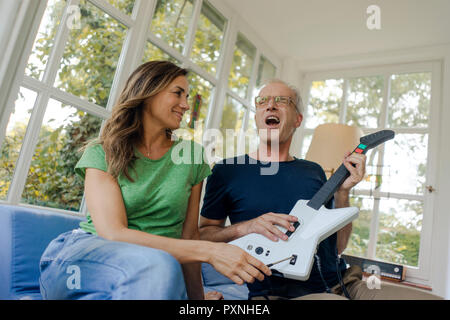 Gerne reifes Paar sitzt auf der Couch zu Hause mit Spielzeug E-Gitarre - Stockfoto