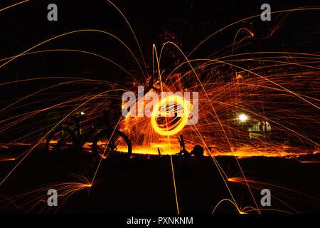 Brennende Stahlwolle spinned im Wald. Duschen glühende Funken von spinning Stahlwolle. - Stockfoto
