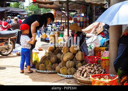 DA LAT, VIETNAM - 23. SEPTEMBER: eine vietnamesische Frau mit einem Kind kauft Durian auf der Straße Markt am 23. September 2018 in Da Lat, Vietnam. - Stockfoto