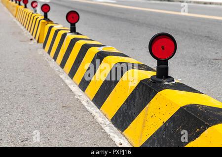 Betonsteine mit gestreiften Vorsicht Muster, Straße Zaun mit roten Reflektoren - Stockfoto