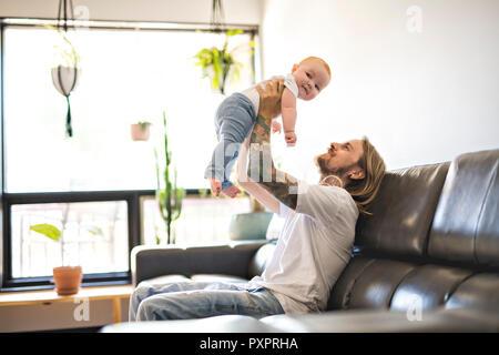 Vater mit Tochter auf dem Sofa zu Hause - Stockfoto