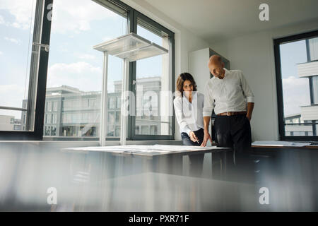 Zwei Architekten, die im Büro, diskutieren Blueprints