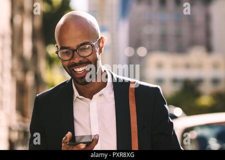 Lächelnden jungen afrikanischen Geschäftsmann pendeln mit einem Handy beim Gehen im Freien. Glatzköpfige Mann im Anzug zu Fuß in die Stadt und spricht auf dem Mobiltelefon - Stockfoto