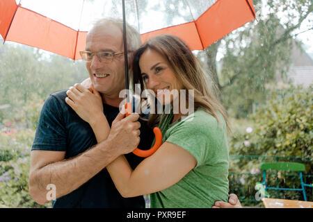 Lächelnd reifes Paar im Regen unter dem Dach - Stockfoto