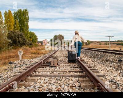 Eine traurige blonde Frau mit einem Strohhut zu Fuß auf den Gleisen, die einen Koffer im Herbst - Stockfoto