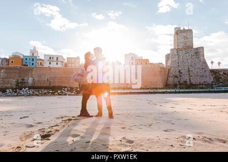 Italien, Molise, Campobasso, junges Paar am Strand bei Sonnenaufgang - Stockfoto
