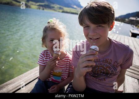 Österreich, Tirol, Walchsee, Portrait von Bruder und Schwester sitzen auf Steg am See essen Eis Kegel - Stockfoto
