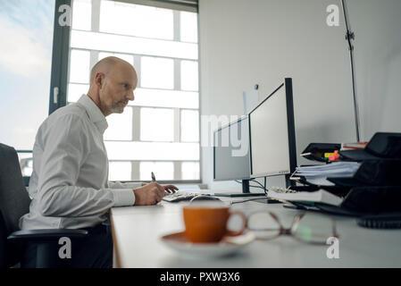 Geschäftsmanns, der auf seinem Computer, Notizen