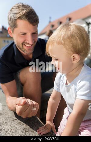 Vater Bilden einer Faust lächelnd an kleine Tochter im Freien - Stockfoto