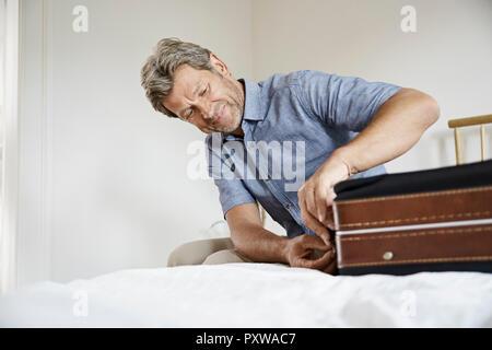 Reife Männer packen Koffer im Schlafzimmer - Stockfoto