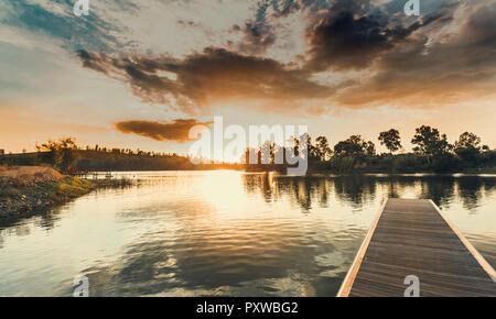 Holzsteg bei Sonnenuntergang mit den orangefarbenen Himmel und die Sonne versteckt sich hinter der Eukalyptus Bäume und den bewölkten Himmel im Hintergrund - Stockfoto