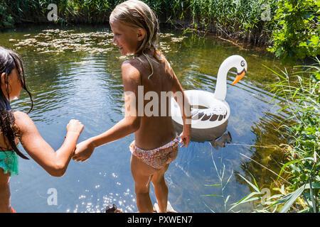 Zwei Mädchen in einem Teich mit aufblasbaren Pool Spielzeug in Swan Form - Stockfoto