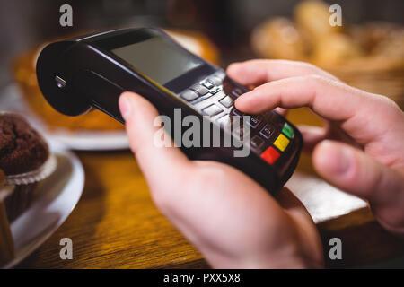 Kunden die Zahlung durch Payment Terminal an der Theke im Cafe - Stockfoto