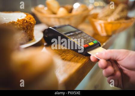 Kunden die Zahlung durch Payment Terminal am Zähler in café - Stockfoto