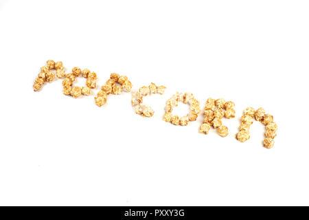 Das Wort POPKORN aus Stücken von Karamell Popcorn auf einem weißen Hintergrund. - Stockfoto