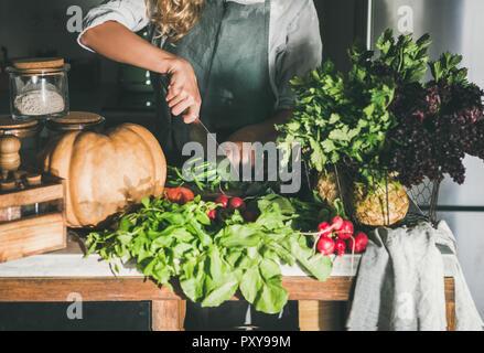 Frau in der Schürze Schneiden von verschiedenen pflanzlichen Zutaten auf Zähler - Stockfoto