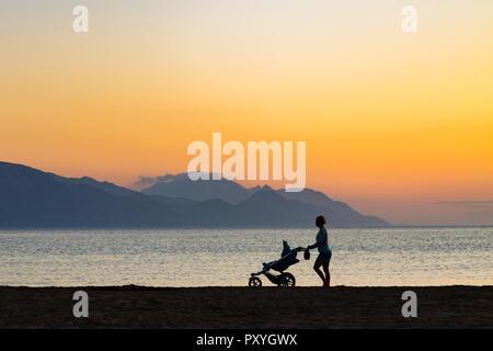 Mutter mit Baby Stroller genießen Mutterschaft bei Sonnenuntergang Landschaft. Joggen oder Frau mit Kinderwagen am Strand bei Sonnenuntergang. Schöne inspirierende Mo - Stockfoto