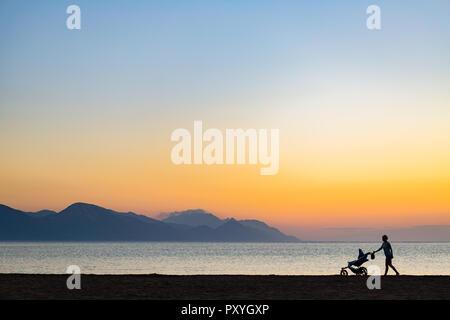 Silhouette von Mutter mit Baby Stroller genießen Mutterschaft bei Sonnenuntergang Landschaft. Joggen oder Frau mit Kinderwagen am Strand bei Sonnenuntergang. Schön in - Stockfoto