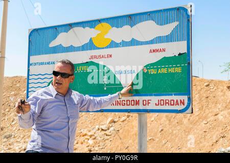 Taille, geschossen von reifer Mann in Sonnenbrille zeigt zur Veranschaulichung Meeresspiegel im Vergleich zum Toten Meer Höhe Ebene zu unterzeichnen, Madaba Governorate, Jordanien - Stockfoto