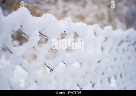 Maschendrahtzaun in einer dicken weißen frischem weichem Schnee gegen einen unscharfen Hintergrund abgedeckt. Kalten Wintertag im Januar - Stockfoto