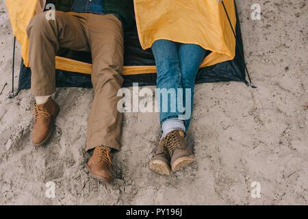 7/8 Schuß von Paar ruht im Camping Zelt am Sandstrand - Stockfoto