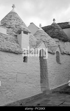 Weiß - konische überdachte Trulli Haus hinter der weißen Wand in der Stadt Alberobello in Apulien, Süditalien gewaschen. In schwarzweiß fotografiert. - Stockfoto