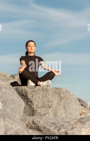 Frau sitzt auf Felsen mit Yoga und Meditation - Stockfoto