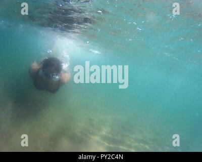 Frau Schwimmen unter Wasser im Meer, Apulien, Italien - Stockfoto