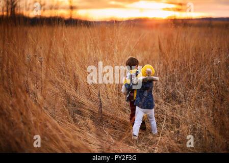 Junge und Mädchen ungefähr in einem Feld bei Sonnenuntergang, United States - Stockfoto