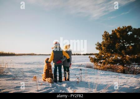 Jungen und Mädchen mit ihrem Hund in einem schneebedeckten Feld, United States - Stockfoto
