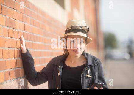 Porträt einer lächelnde Frau mit der Hand lehnte sich an eine Wand - Stockfoto