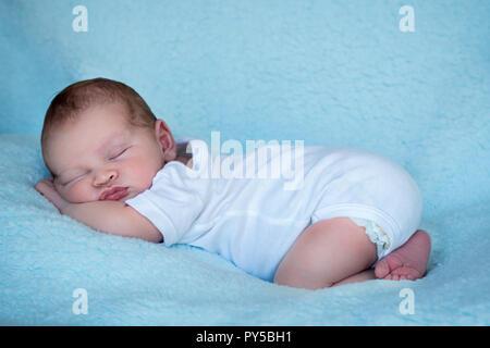 Neugeborene schlafen auf seinen Bauch voller länge Seite Profil blauer Hintergrund - Stockfoto