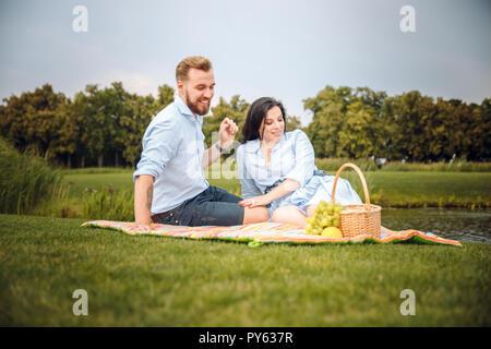 Glückliche freudige junge Familie Mann und seine schwangere Frau Spaß zusammen im Freien, im Sommer Picknick im Park, auf dem Land. - Stockfoto