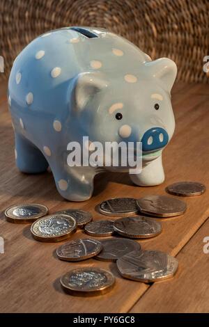 Hellblau Sparschwein mit weißen Punkten, und dem britischen Pfund Sterling Münzen um es in einem hellen Holz- Oberfläche. Sparen Sie bares Geld. Home Finance - Stockfoto