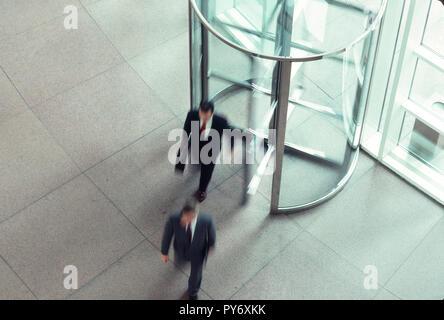 Unternehmer im Bürogebäude Drehtür, USA - Stockfoto