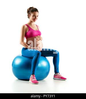 Lächelnd schwangere Frau in Sportkleidung sitzen auf Fit Ball berühren und ihren Bauch auf weißem Hintergrund. Konzept des gesunden Lebens - Stockfoto
