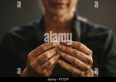 In der Nähe der weiblichen Juwelier Hände Prüfung Ring an der Werkstatt. Fokus auf Frau Schmuckhersteller Hände Inspektion ein silberner Ring. - Stockfoto