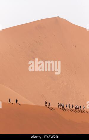 Touristen wandern auf dem Kamm einer Düne; Big Daddy Dune im Hintergrund; Sossusvlei, Namib, Namibia Afrika - Stockfoto