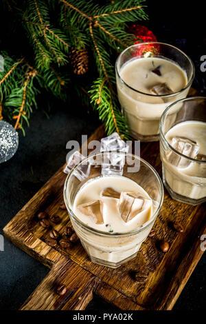 Irish Cream Likör, Cocktail oder traditionellen Winter Weihnachten trinken, dunklen Rusty Hintergrund mit Fir Tree Branches, Kaffeebohnen und Weihnachten Dekoration