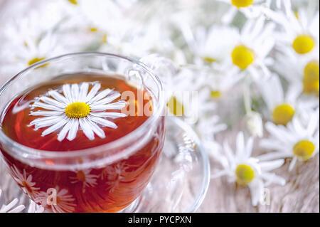 Eine klare Schale von Arzneimitteln Kamille Tee auf einem alten Holztisch. Gesundheit und gesunder Lebensstil Konzept. - Stockfoto