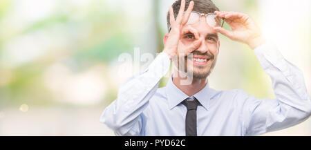 Young Business Mann mit glücklichen Gesicht lächelnd tun ok Zeichen mit der Hand auf Auge schauen durch die Finger