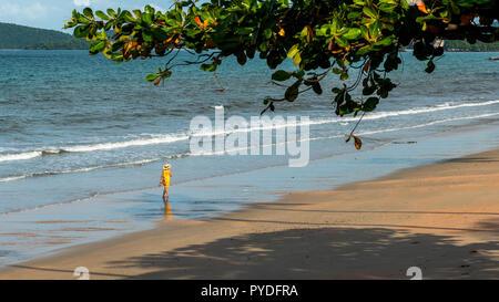 Frau im gelben Kleid zu Fuß den Strand runter - Stockfoto