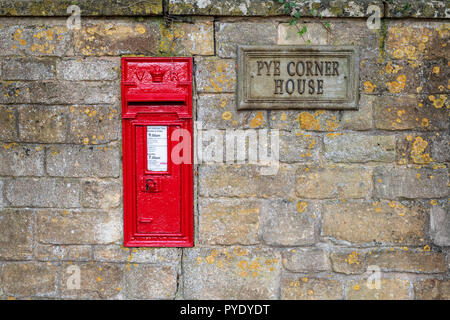 Red Post Box in einem cotswold stone wall. Broadway, Worchestershire, Cotswolds, England - Stockfoto