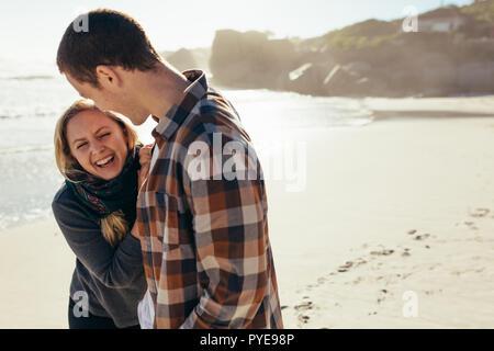 Junge Frau lachend mit ihrem Freund am Strand. Liebevolle junge Paar eine tolle Zeit am Strand. - Stockfoto