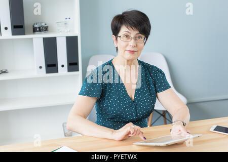 Unternehmen und Personen Konzept - selbstbewusste Frau mittleren Alters ist die Arbeit mit Tablet-PC im Büro - Stockfoto