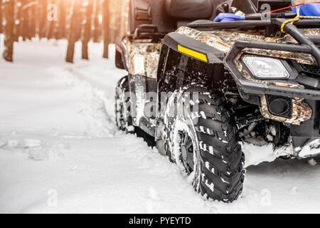 Close-up ATV Allrad Quad Bike im Wald im Winter. 4WD-Fahrzeug terreain stand bei starkem Schneefall mit tiefen Spur. Saisonale extreme Sport Abenteuer und Reise. Copyspace - Stockfoto