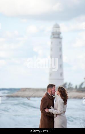 Glückliche junge Mann im Mantel umarmen Freundin auf windigen Küste mit Leuchtturm im Winter - Stockfoto